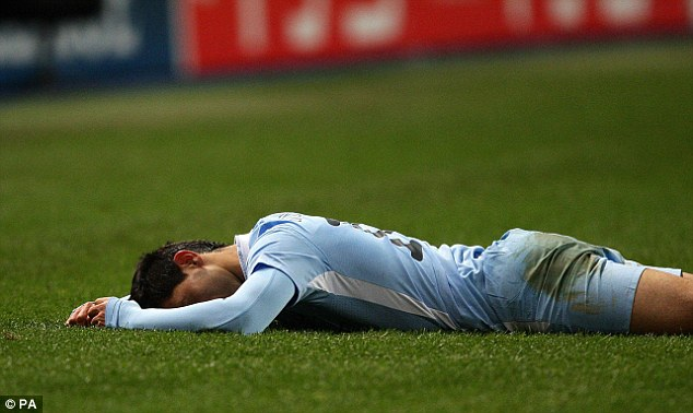 Sergio Agüero laying on the grass after Manchester City were eliminated